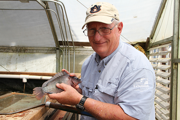 Jesse Chappell holds a fish in a greenhouse.