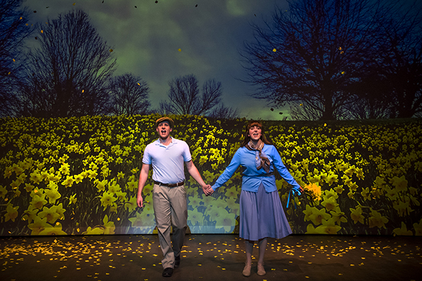 A man and woman hold hands as they walk through a field of daffodils during a production of Big Fish.