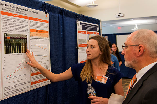 Student Elizabeth Bankston discusses her poster with Steve Taylor, chair of the Research Symposia Committee, at last year's symposium.