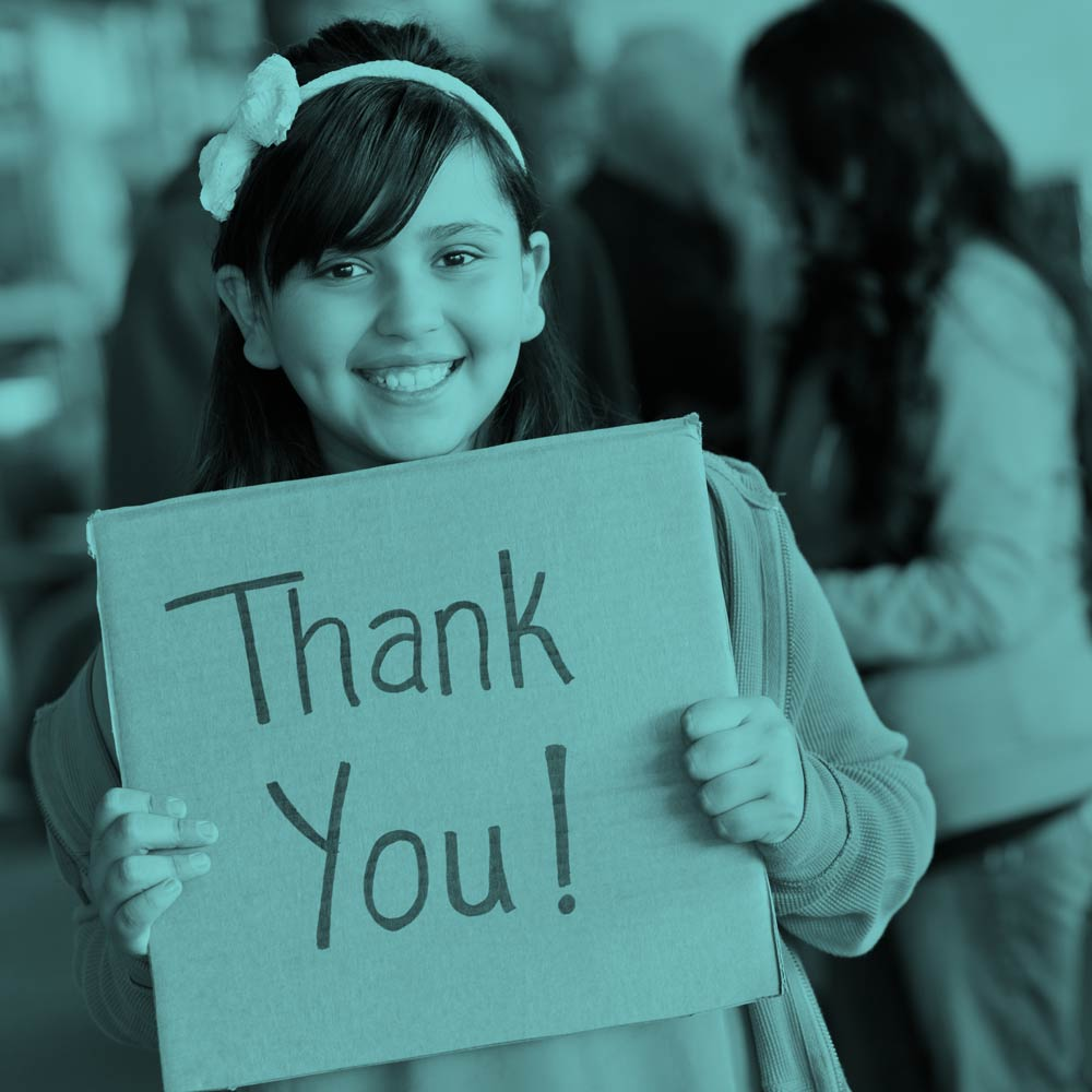 A young girl holds a Thank You sign