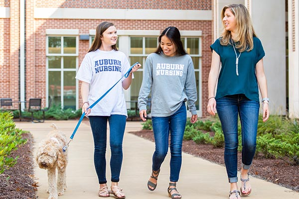 nursing students walking with Daisy, a goldendoodle