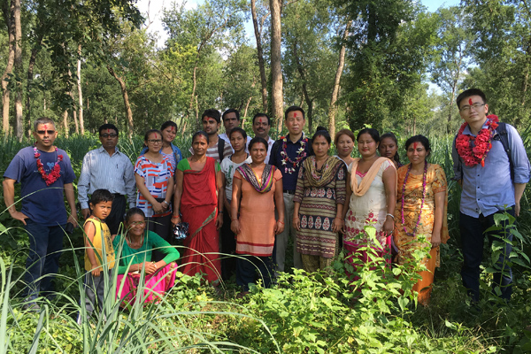 Daowei Zhang is pictured with community members near a village in Nepal.